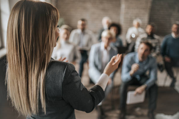 Female manager talking to large group of her colleagues on a business seminar. Back view of female public speaker giving a presentation to large group of business people in a board room. speech stock pictures, royalty-free photos & images