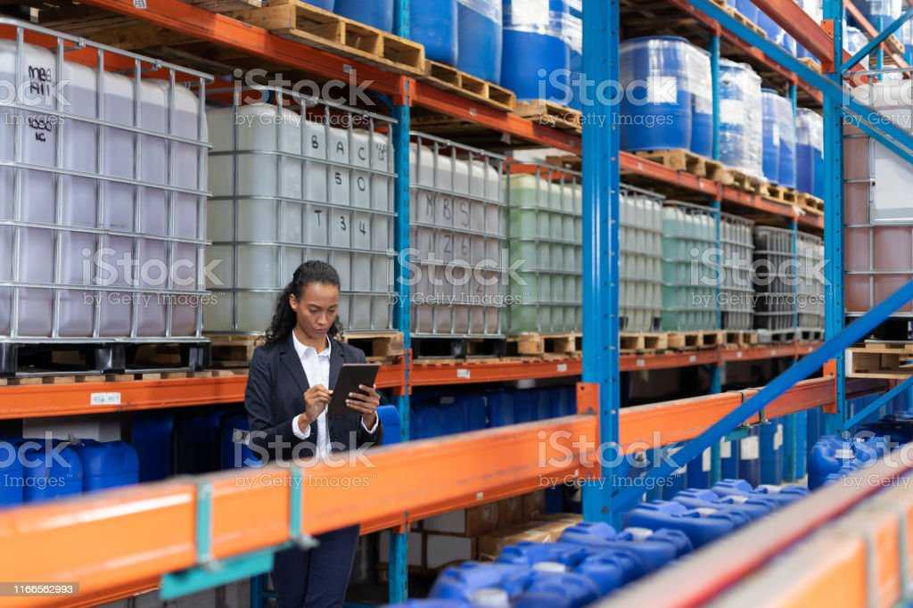African American female manager using digital tablet in warehouse....