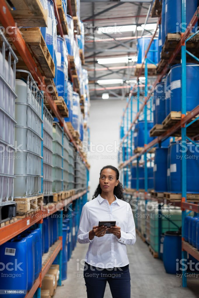 African American female manager using digital tablet while checking...