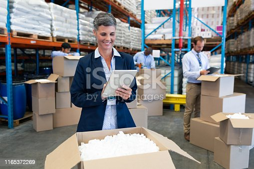 1165379503istockphoto Female manager working on digital tablet in warehouse 1165372269
