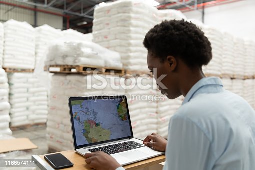 Rear view of female manager working on laptop at desk in warehouse. This is a freight transportation and distribution warehouse. Industrial and industrial workers concept