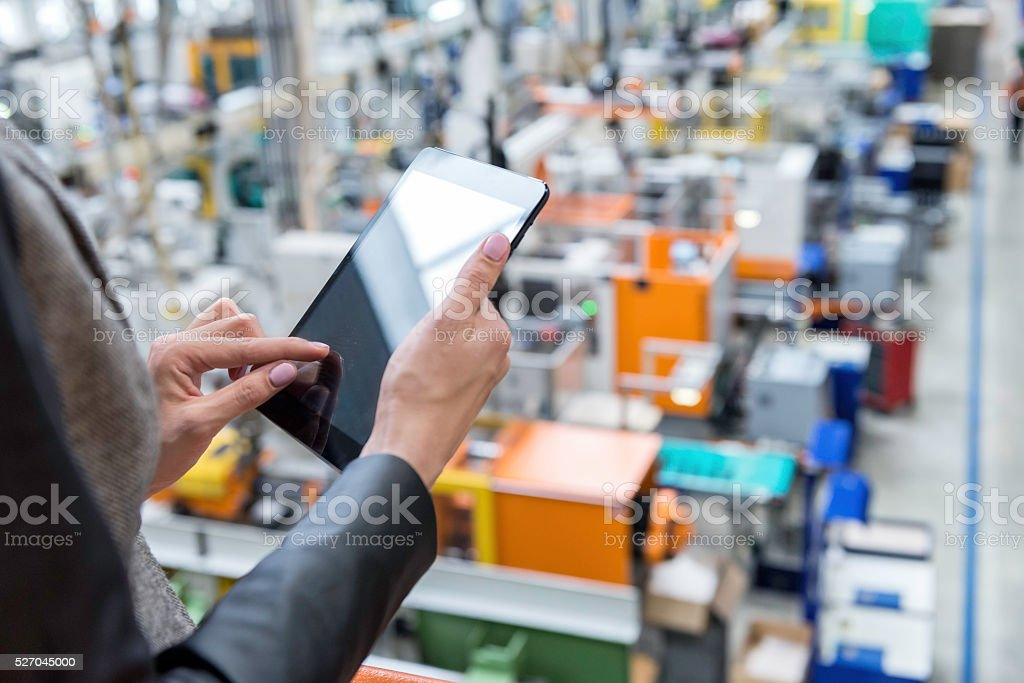 Female manager working on tablet in factory stock photo