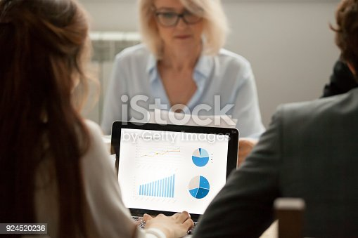 istock Female manager working with project statistics on laptop at meeting 924520236