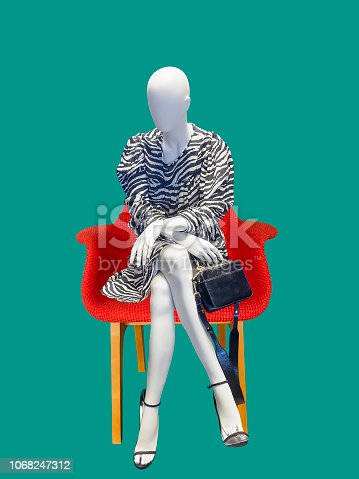 Female mannequin sitting on red armchair, against blue background. No brand names or copyright objects.