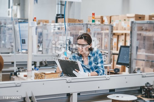 Professional young industrial factory woman employee working with machine parts taking necessary notes with a notepad and a pen while inspecting industrial machine checking and testing industrial equipments cables in large electronics factory warehouse