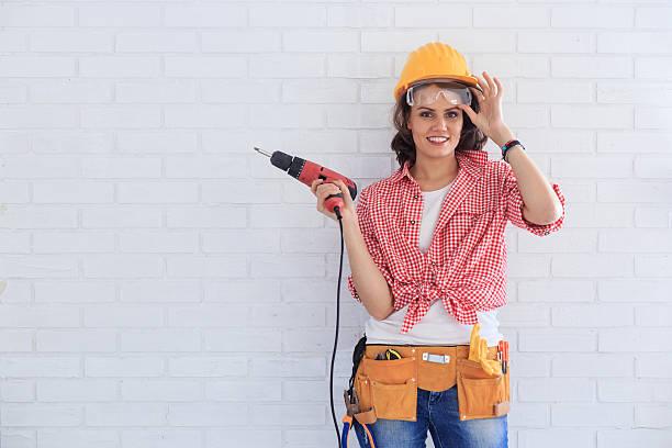 Female manual worker using screwdriver stock photo