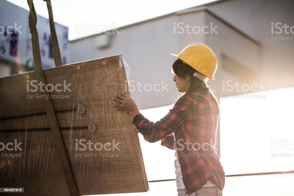 Female manual worker working with construction equipment on a balcony. - Royalty-free Adult Stock Photo
