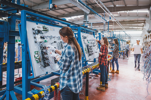 Inpector man checking professional young industrial factory women employee working with machine parts putting, checking and testing industrial equipments cables in large Electric electronics wire and cable manufacturing plant factory warehouse