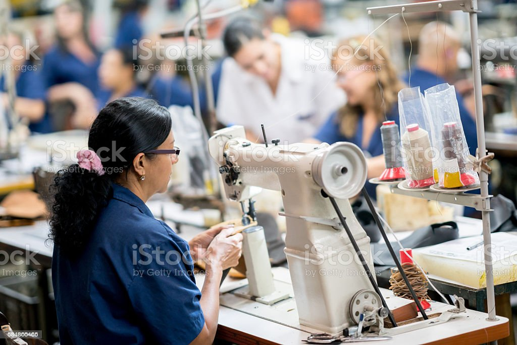 Female manufacturing worker at a shoe-making factory stock photo