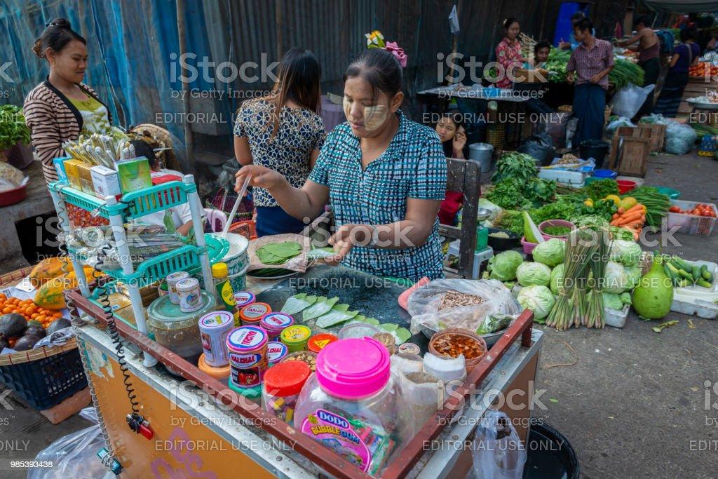 Vrouwelijke markt verkoper voegt kalk plakken te betel bladeren, markt in Yangon, Myanmar foto
