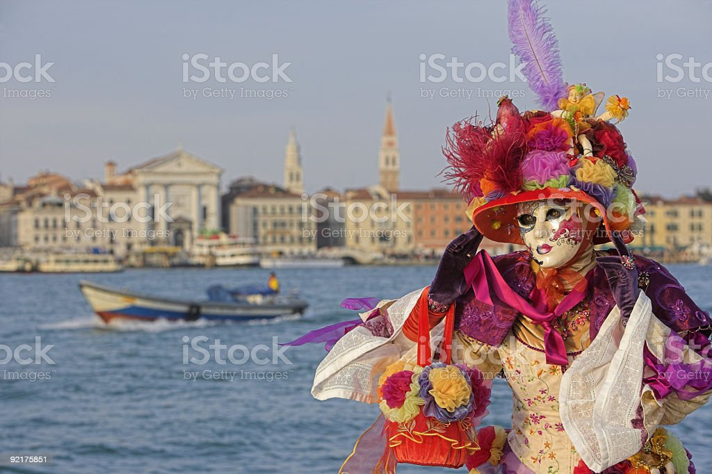 Female mask with colorful costume at Grand Canal in Venice stock photo