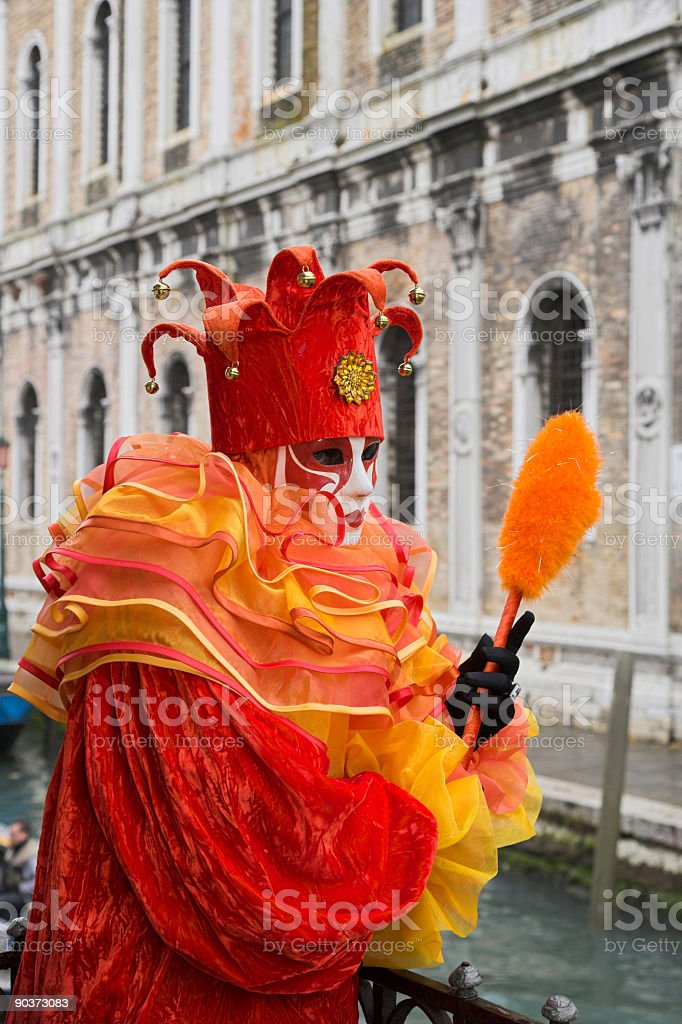 Female mask with harlequin costume and historical facade in Venice royalty-free stock photo