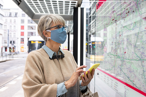 Female masked commuter looking at the bus line on map