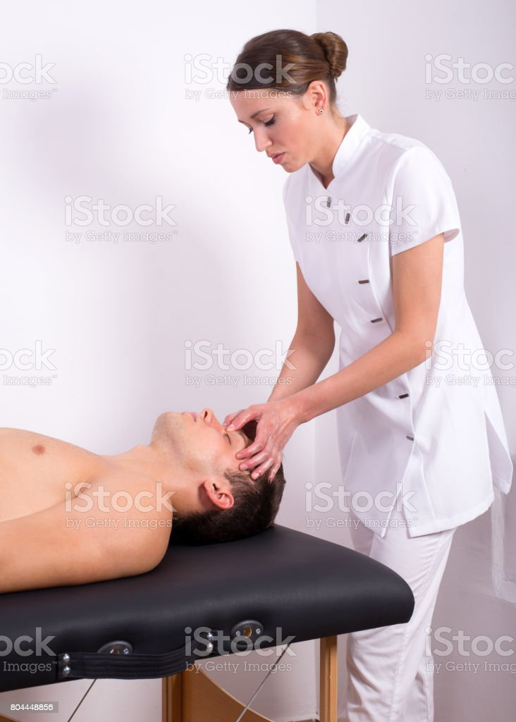 Female massage therapist giving face massage to young man lying on...