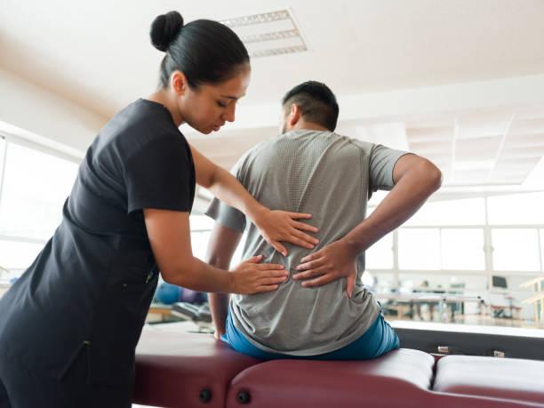 Female massage therapist massaging patient's back stock photo