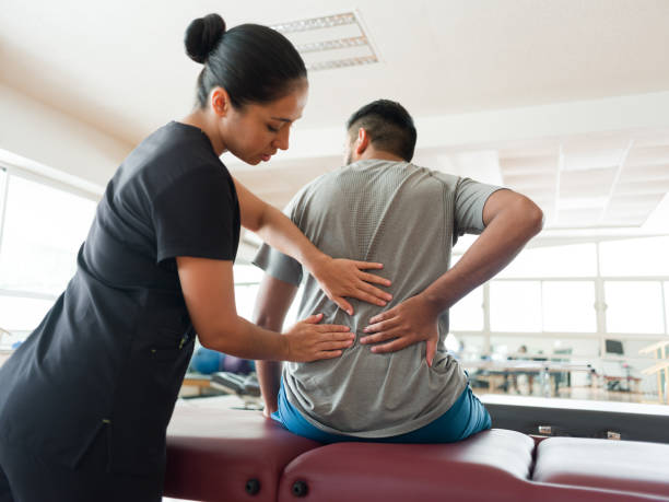 Female massage therapist massaging patient's back A female massage therapist standing behind a male patient and massaging his back with both hands. sports medicine stock pictures, royalty-free photos & images