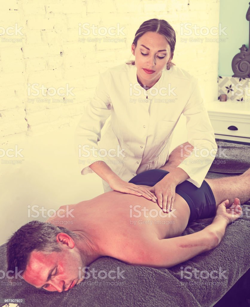 Female massagist doing massage to male client stock photo