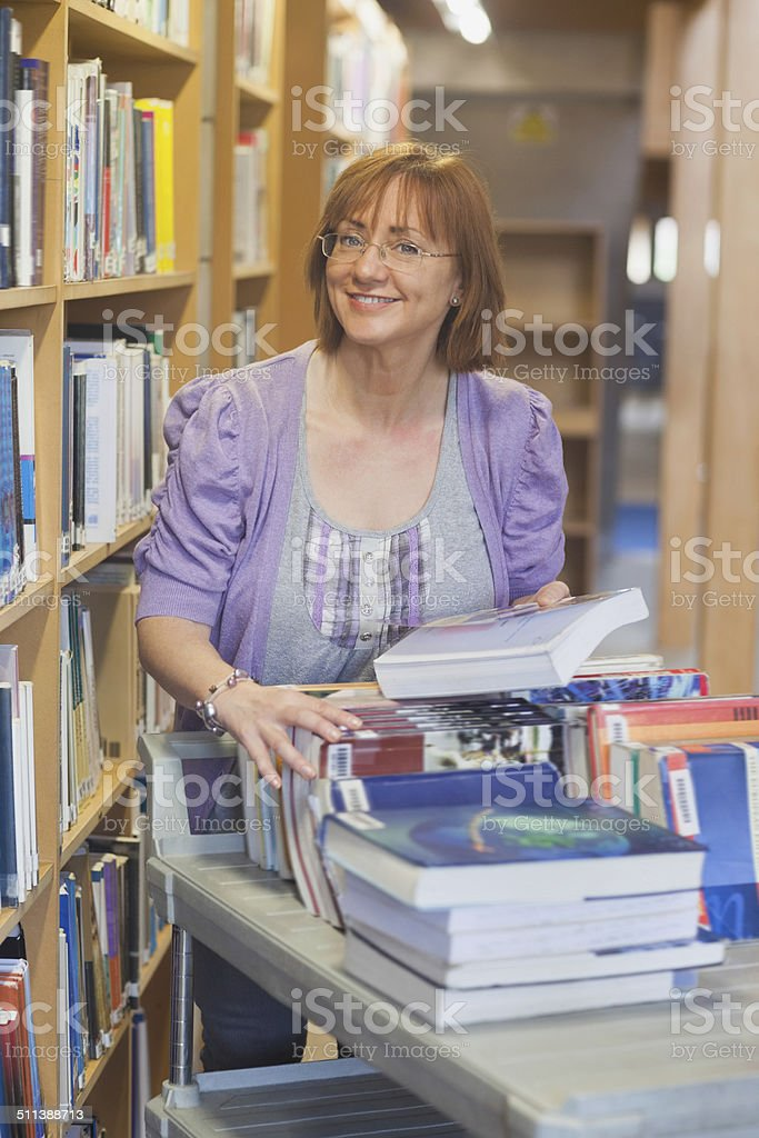 Female mature librarian returning books in library stock photo