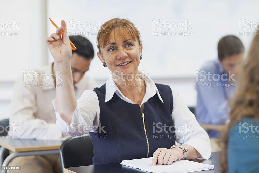 Female mature student raising her hand bildbanksfoto