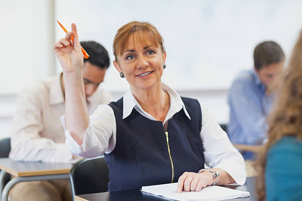 female mature student raising her hand - adult education stock pictures, royalty-free photos & images