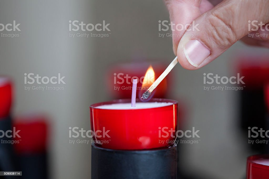 Female mature woman burning candle light in church stock photo