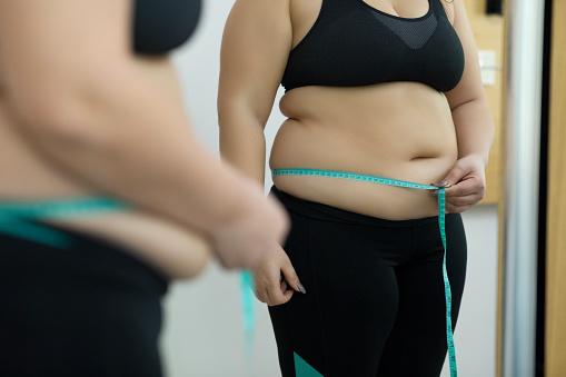 Female measures her waist