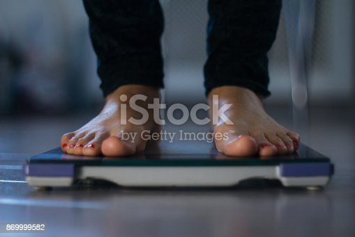 Female measuring weight on health scale close-up. Woman legs approaching to weighing digital instrument