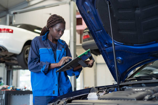 female mechanic checks with handheld the error memory of a car stock photo