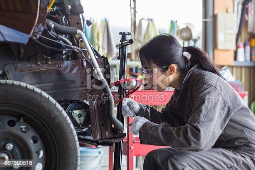 Female mechanic fixing a damaged car in an auto repair shop