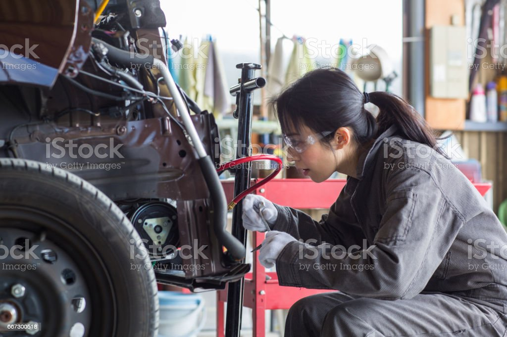 Female mechanic fixing a damaged car in an auto repair shop stock photo
