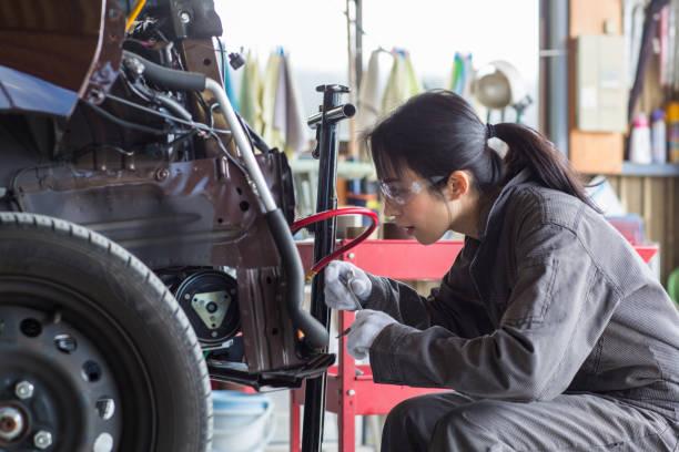 Female mechanic fixing a damaged car in an auto repair shop stock photo
