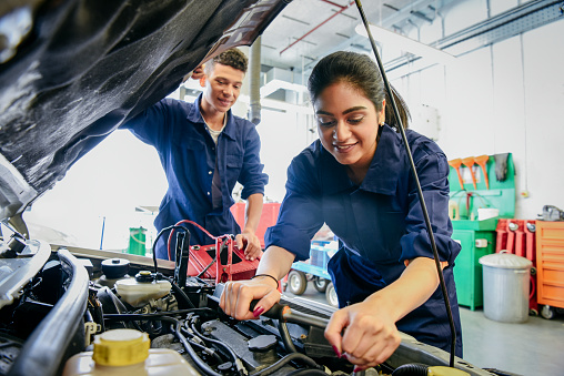 Two car mechanic students working in garage at FE college, young woman learning mechanical skills