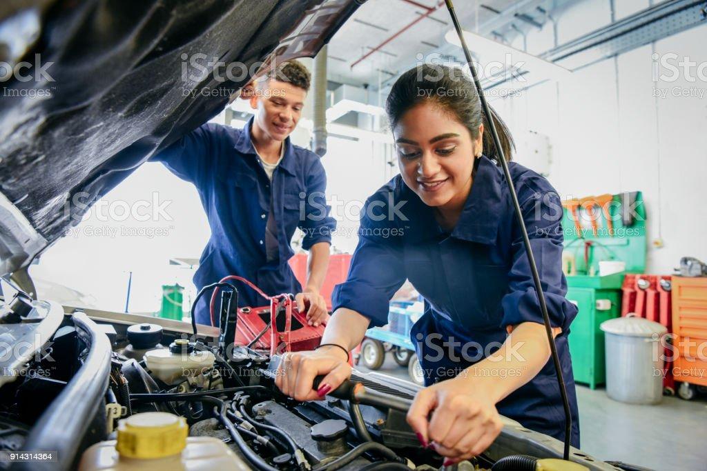 Female mechanic fixing car, young man watching stock photo