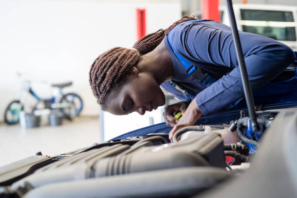 female mechanic looks with flashlight at the machine of a car stock photo