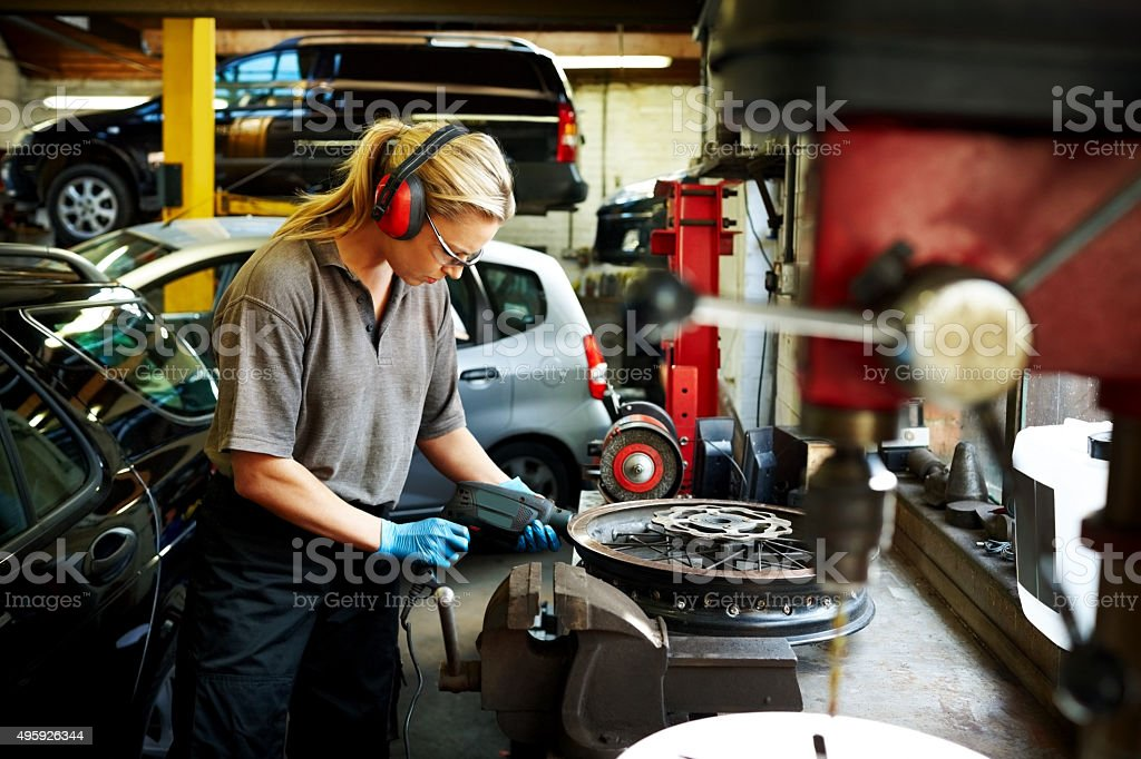 Female mechanic working in auto garage stock photo
