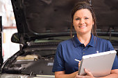 Latin descent, female mechanic working in an automobile repair shop.  The female mechanic is writing up an invoice for the customer regarding the vehicle's engine troubles.  She wears a blue uniform.