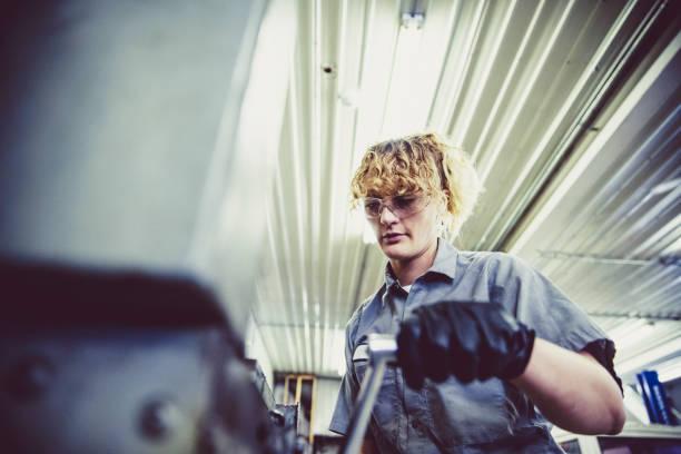 Female Mechanic Working on a Heavy Machinery stock photo