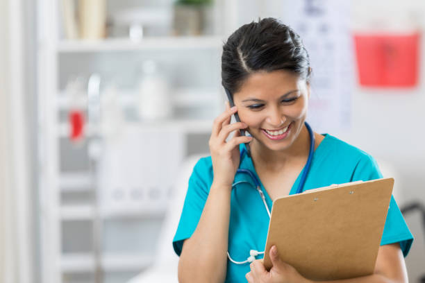 female medical doctor discusses patient diagnosis on phone - nurse on phone stock photos and pictures