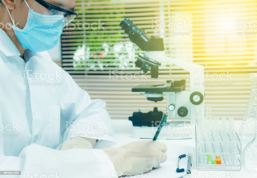 Female medical or scientific researcher or woman doctor writing on the document in a laboratory with microscope and other equipment in the foreground,science people and selective focus. royalty-free stock photo