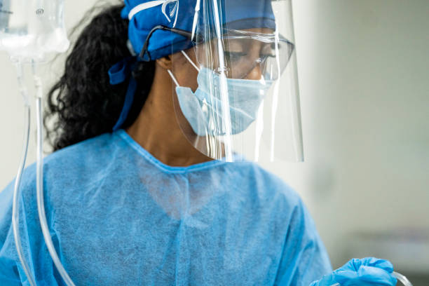Female medical professional about to administer IV drip stock photo
