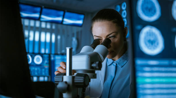 female medical research scientist looking through the microscope types acquired data in the computer. laboratory. in the laboratory with multiple screens showing mri / ct brain scan images. - medical research stock pictures, royalty-free photos & images
