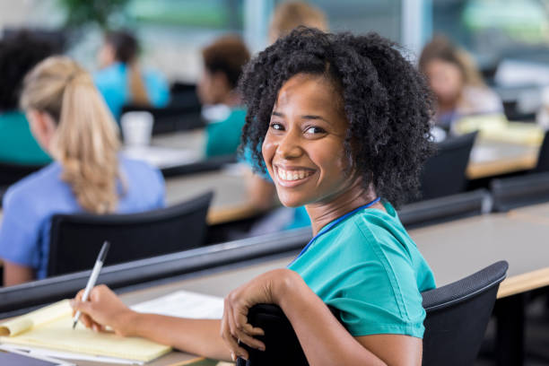 Female medical student turns to smile for camera stock photo