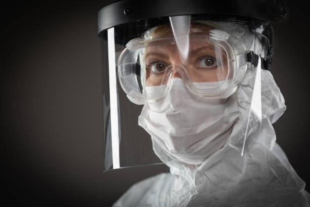 Female Medical Worker Wearing Protective Face Mask and Gear Against Dark Background Female Medical Worker Wearing Protective Face Mask and Gear Against Dark Background. protective workwear stock pictures, royalty-free photos & images
