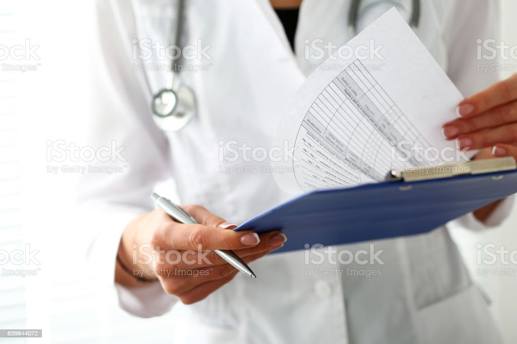 Female medicine doctor hand holding silver pen stock photo