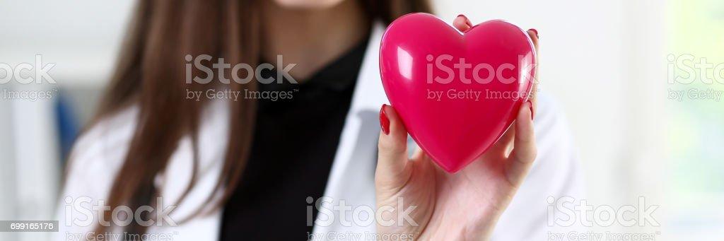 Doctor en medicina femenina manos sosteniendo corazón rojo - foto de stock