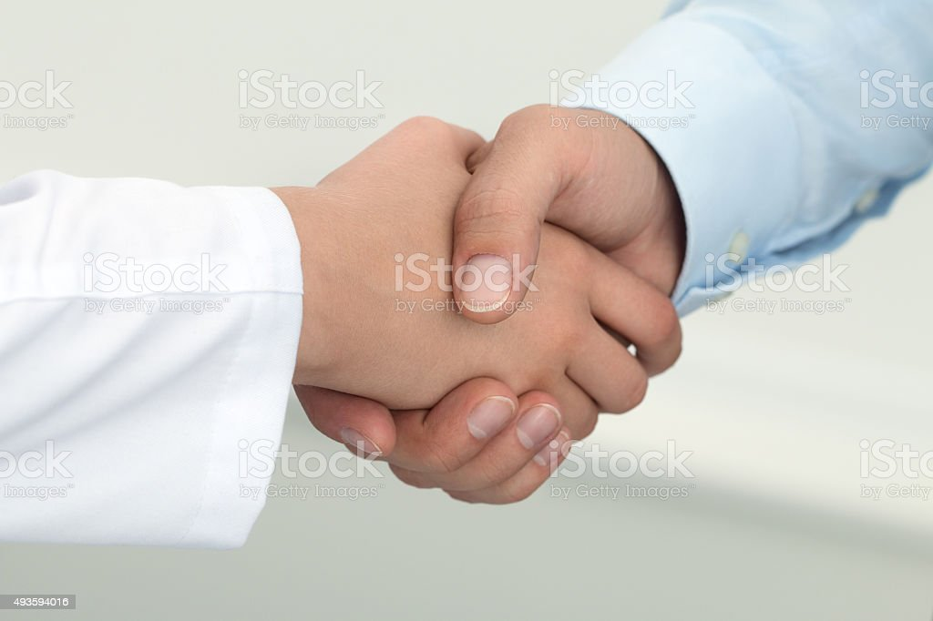 Female medicine doctor shaking hands with male patient. stock photo