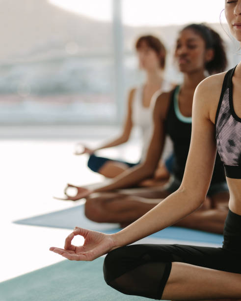 Female meditating in lotus pose at yoga class Women sitting on exercise mat with legs crossed and hands on knees. Female meditating in lotus pose at yoga class, Padmasana. Cropped shot with focus on hand of women in front. yoga class stock pictures, royalty-free photos & images