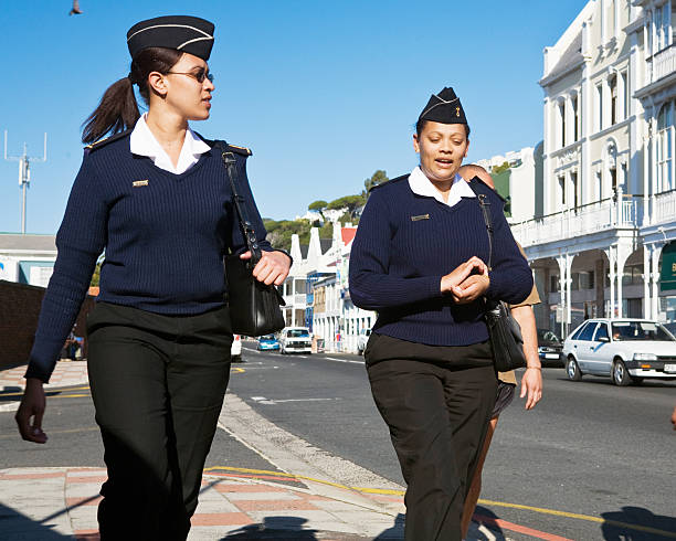 Female members of South African Navy walking in Simon's Town Cape Town, South Africa - September 17, 2007: Female members of the South African Navy, in uniform, chat as they walk past Victorian buildings in the main street of Simon's Town, a coastal village near Cape Town whose harbour is the home of South Africa's modest naval force. naval base stock pictures, royalty-free photos & images