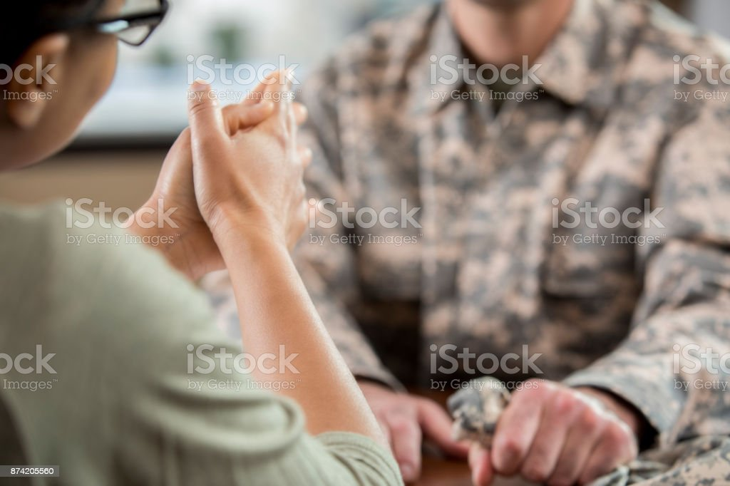 Female mental health professional counsels soldier with PTSD stock photo