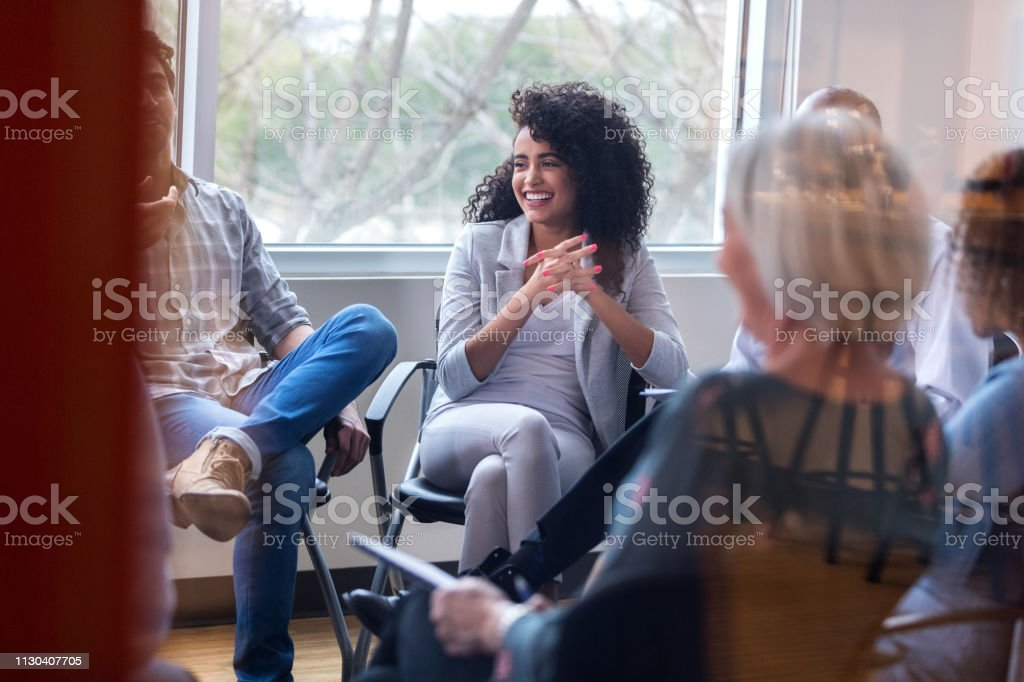 Young female mental health professional smiles while encouraging a...